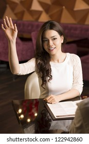 Girl in white beckoning the waiter to come over