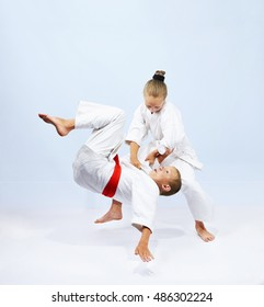 The girl with a white belt does judo throw