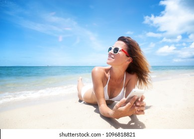 A girl in a white bikini lies on the sand with a mobile phone in hands on the shore of a tropical beach, a connection during a vacation and travel
