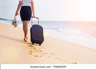 Girl in a white blouse and black skirt in office clothes clerk manager goes away walk on the beach on the sea and sand background with a suitcase on wheels luggage. Go for weekend.