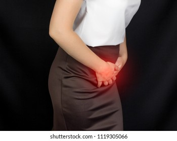 A girl in a white blouse holds onto the groin of the lower abdomen, her stomach hurts, sexual infections, genital infections