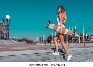 Girl in a white body bathing suit, summer city, goes with board, skate longboard. Free space for text. Long hair sunglasses sneakers. Concepts fashion youth style, trend and fashion modern.