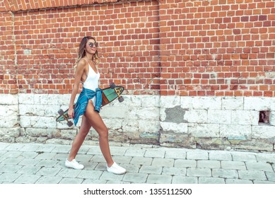 Girl in white bodysuit with jeans, walks in the summer in the city on the background of a brick wall. Happy smiling, tanned skin. Free space for text.