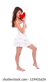 Girl in white clothes holding red heart in front of her face