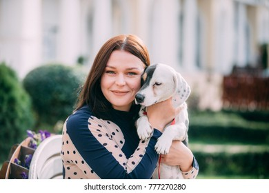 A girl and a white dog with brown spots