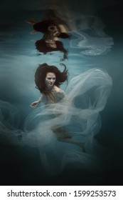 Girl in a white dress with a cloth swims underwater