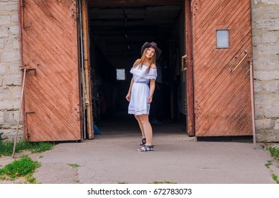 A girl in a white dress and a cowboy hat dancing against the backdrop of a horse at the ranch