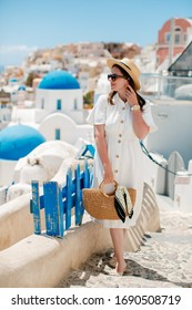 girl in a white dress with glasses on a background of white houses with blue roofs in Santorini