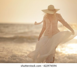 girl in white dress and hat on the beach