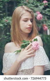 girl in a white dress holds a rose in her hands, a rose on a green background