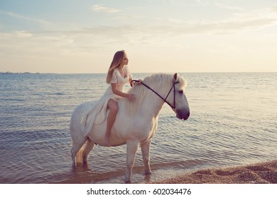 Girl in white dress with horse on the beach