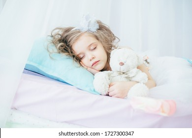 girl in a white dress lies and sleeps in an embrace on a bed on a background of white sheets