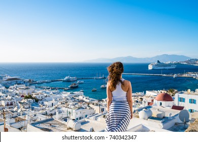 Girl in white dress  looking at Mykonos town, Greece