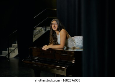 girl in white dress poses lying on a black grand piano on a stage
