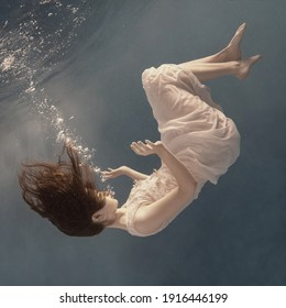 A girl in a white dress posing and somersaulting under water as if flying in zero gravity