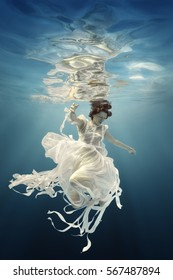 The girl in a white dress with ribbons under water