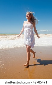 Girl in white dress is running on seashore