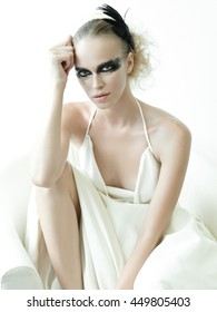 Girl in white dress sitting. Beautiful makeup. Smoky eyes. Like a ballet dancer