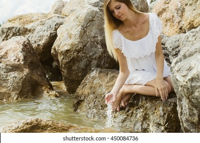 girl in white dress sitting by the sea water touching hands