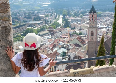 A girl with white dress and straw hat on top of old fortress in Merano,Italy
