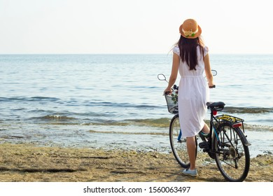 Girl in a white dress and a straw hat with a bicycle in the summer on the seashore, back view.