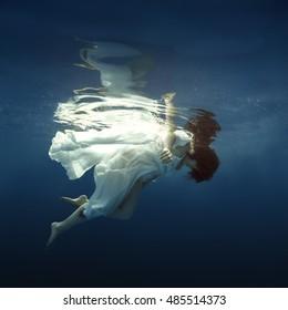 Girl in white dress swimming under water