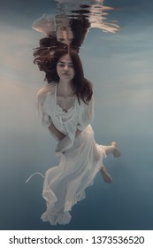The girl in the white dress swims under water