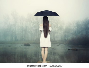 8ef3e8b9741dc Girl in white dress with umbrella. Woman standing on the stone at the river