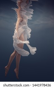 Girl in a white dress under water