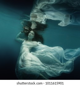 Girl in white dress underwater