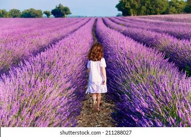 Girl in white dress walking in lavender field