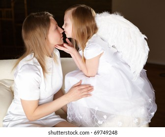 girl in white dressed as an angel kissing a woman