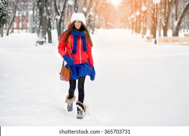 A girl in a white fur hat, a red jacket and blue mittens, walks in the park in winter.