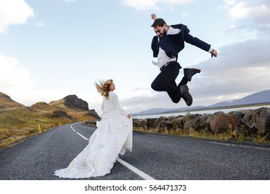 Girl in white gown walking down highway with her groom jumping near by