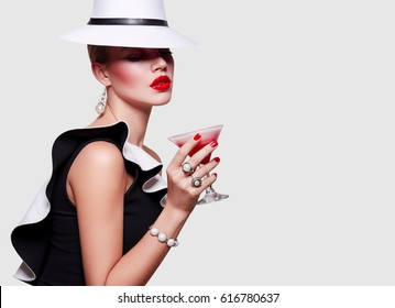 Girl in white hat covers her face. Girl with a glass of cocktail in hand. Girl drinks cocktail. Strawberry milkshake. The charming stranger.