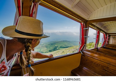 A girl in a white hat pointing scenic mountain views from a train window.