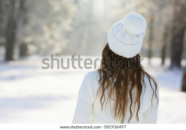 Girl in a white hat with a pompon, standing back in the winter park