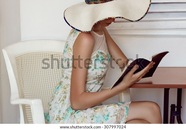 The girl in white hat, reading a book
