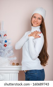 Girl in a white hat and sweater in home interior