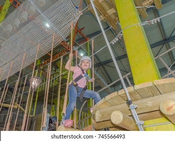 the girl in the white helmet in the adventure Park holds on to the ropes