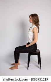 girl in white jacket and black pants barefoot sitting on chair sideways on white background