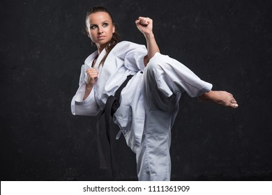A girl in a white kimono with a black belt on a dark background
