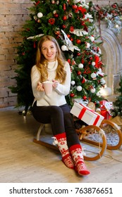 Girl in white knitted jumper, christmas socks with cocoa marshmallow. Winter holidays