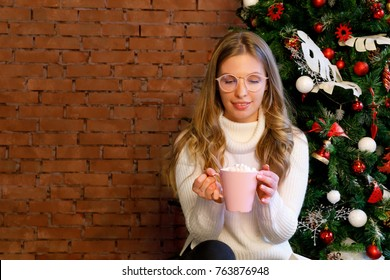 Girl in white knitted jumper, christmas socks with cocoa marshmallow. Brick wall mock up. Winter holidays
