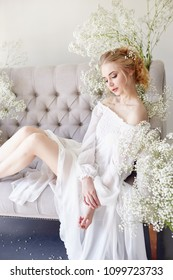 Girl white light dress and curly hair, portrait of woman with flowers at home near the window, purity and innocence. Curly blonde romantic look, beautiful eyes. White wildflowers in hands