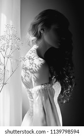 Girl white light dress and curly hair, portrait of woman with flowers at home near window, purity and innocence. Curly blonde romantic look, beautiful eyes. White wildflowers in hands. Black and white
