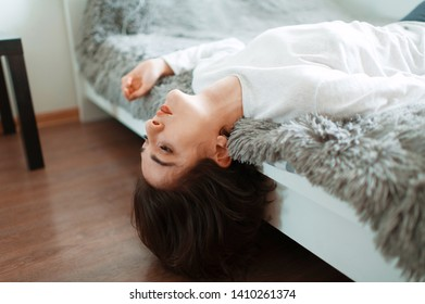 girl in white lying on the bed upside down. head overturned. resting at home