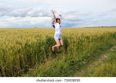 A girl in a white painted shirt in a field of wheat.