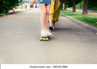 a girl in white paintwork rides a penny board. Outdoor lifestyle picture on a sunny summer day.