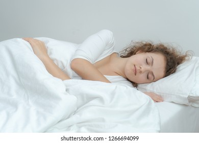 The girl in the white pajamas sleeps happily in the airy white bedroom.